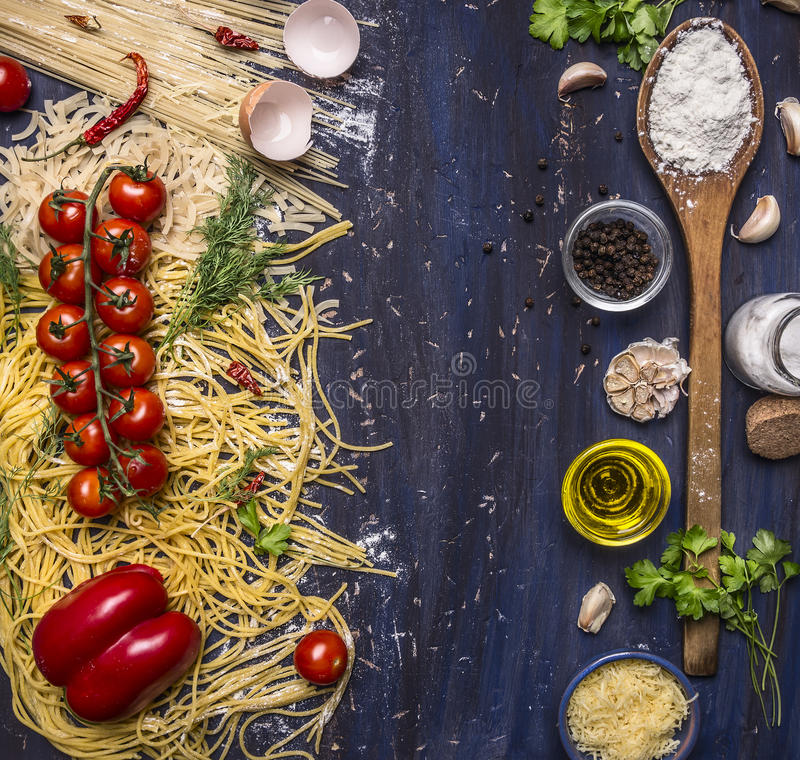 Various raw pasta with vegetables and spices, flour and wooden spoon frame with text area wooden rustic background top view stock photography