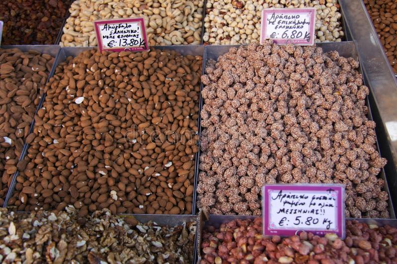 Roasted nuts on a market stall. Various roasted nuts, including almonds, walnuts, cashew nuts, hazelnuts, ground nuts in shell, as well as dried fruit, such as royalty free stock photo