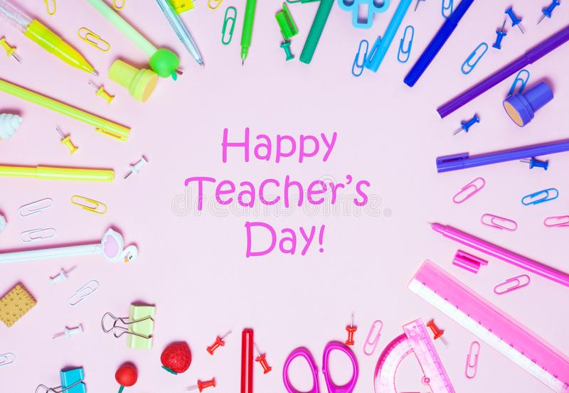 Various School accessories are laid out in the form of a rainbow, Happy Teacher`s day text. stock photo