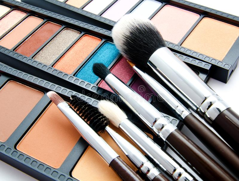 Various set of professional makeup brushes and palette of colourful eye shadows stock photography