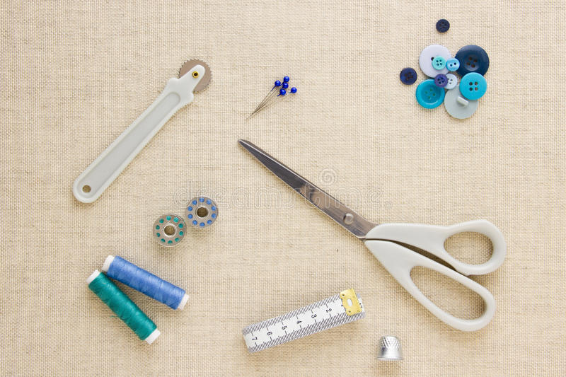 Sewing accessories in blue tones. Various sewing items, including scissors, tailors wheel, bobbins, spools of thread, measuring tape, thimble and buttons in stock image