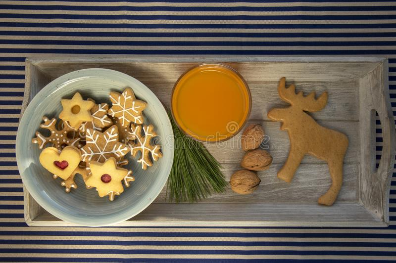 Various shapes of Christmas gingerbread cookies on light blue bowl on wooden table, group of simplicity winter sweets royalty free stock photos