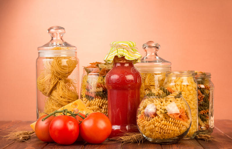 Various shapes pasta in jars, bottle ketchup, tomato on brown. royalty free stock image