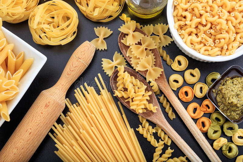 Various shapes of raw pasta on black background stock image