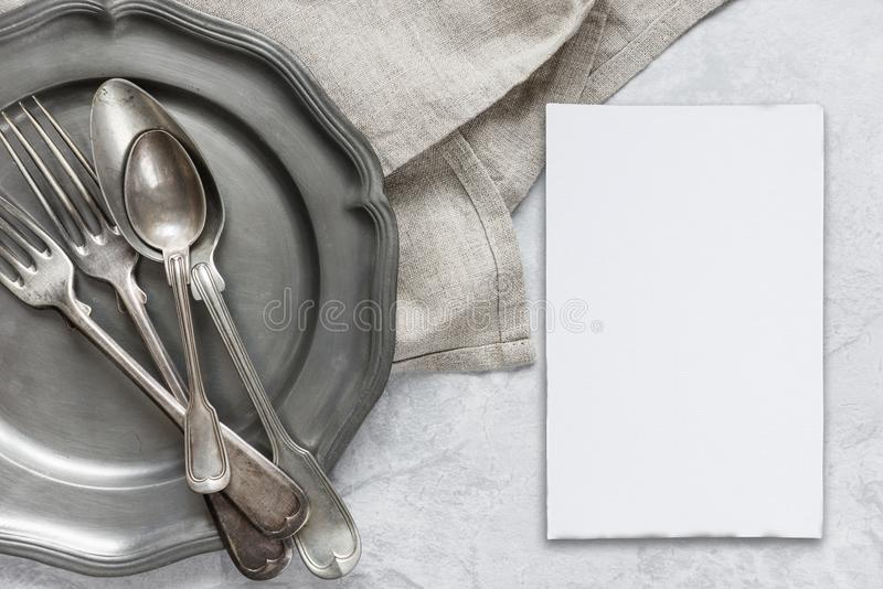 Silverware on a pewter plate. Various silverware on a pewter plate, gray flax napkin and white blanc paper card are on the background of gray concrete surface royalty free stock photos