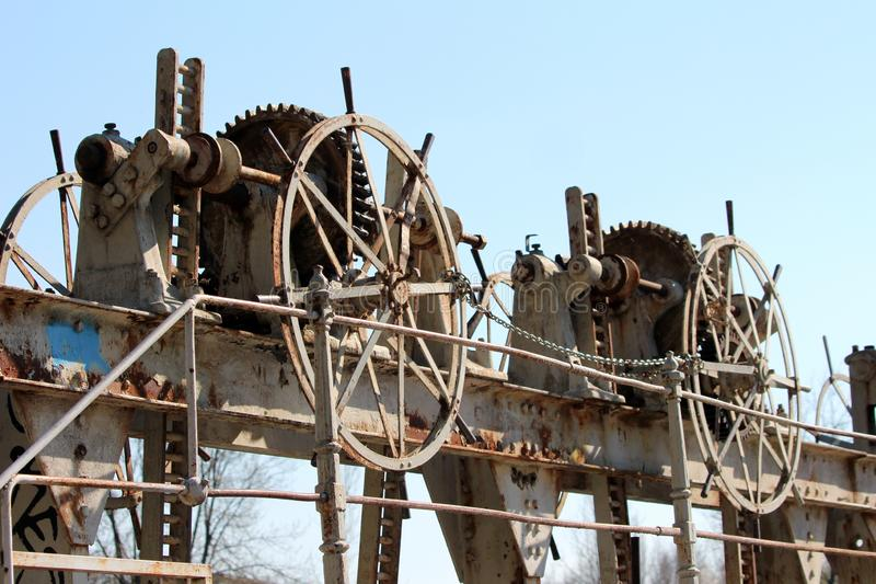 Various size cogwheel rusted gears at abandoned dam locked with small chain to prevent unauthorized usage. On clear blue sky background royalty free stock photo