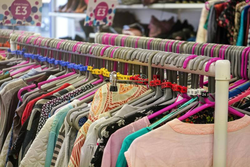 Various sizes of ladies clothes displayed on hangers in charity thrift shop stock image