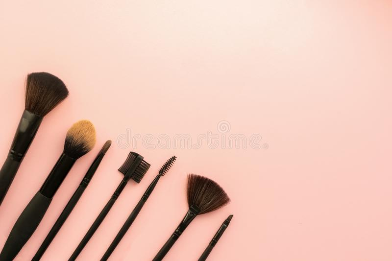 Various small brushes small for applying decorative makeup on a delicate pink background. Care and beauty concept. stock image