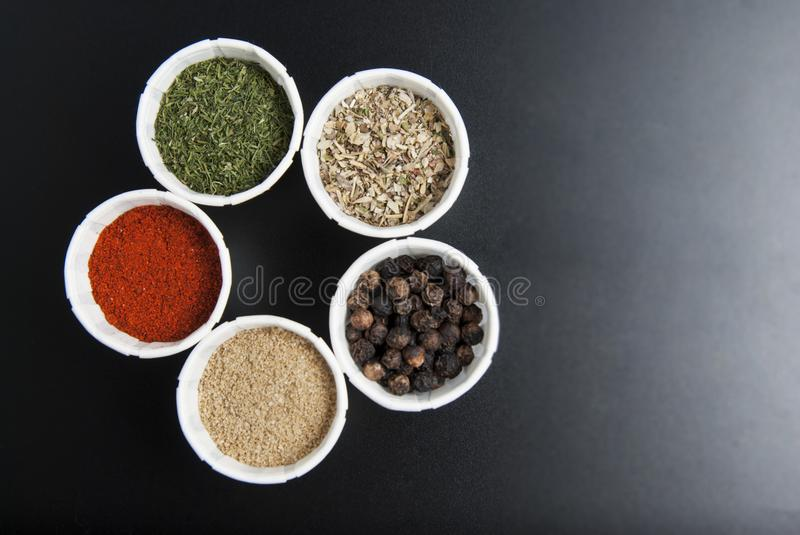 Various spices on black background: rosemary, paprika, black pepper. Top view. Copy space. Various spices on black background: rosemary, paprika, black pepper royalty free stock photos