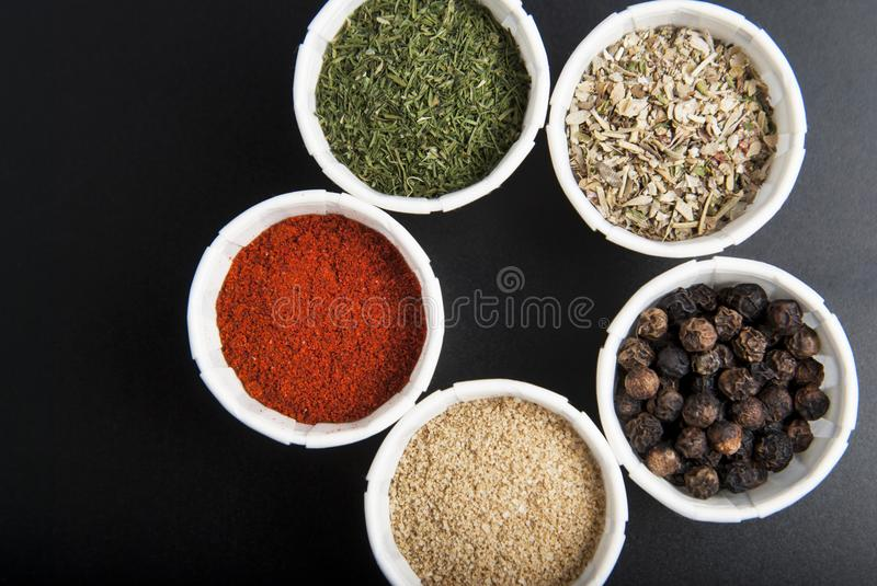 Various spices on black background: rosemary, paprika, black pepper. Top view. Copy space. Various spices on black background: rosemary, paprika, black pepper royalty free stock photo