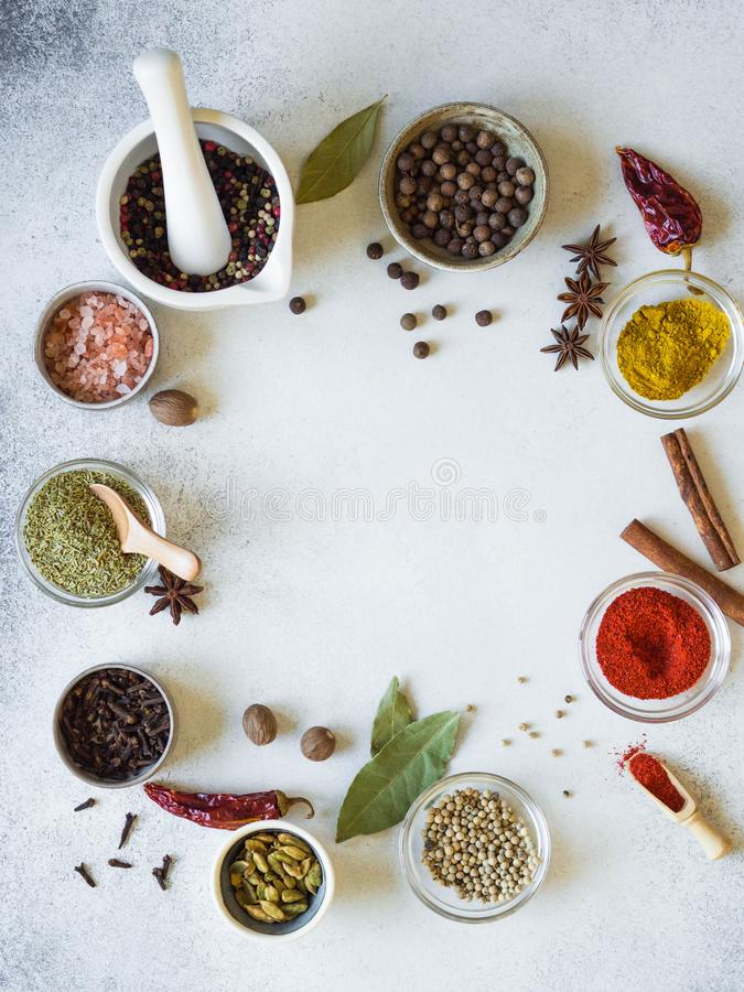 Various spices in bowls and pestle frame on the table. dry herbs, salt spices on a gray background. royalty free stock photos