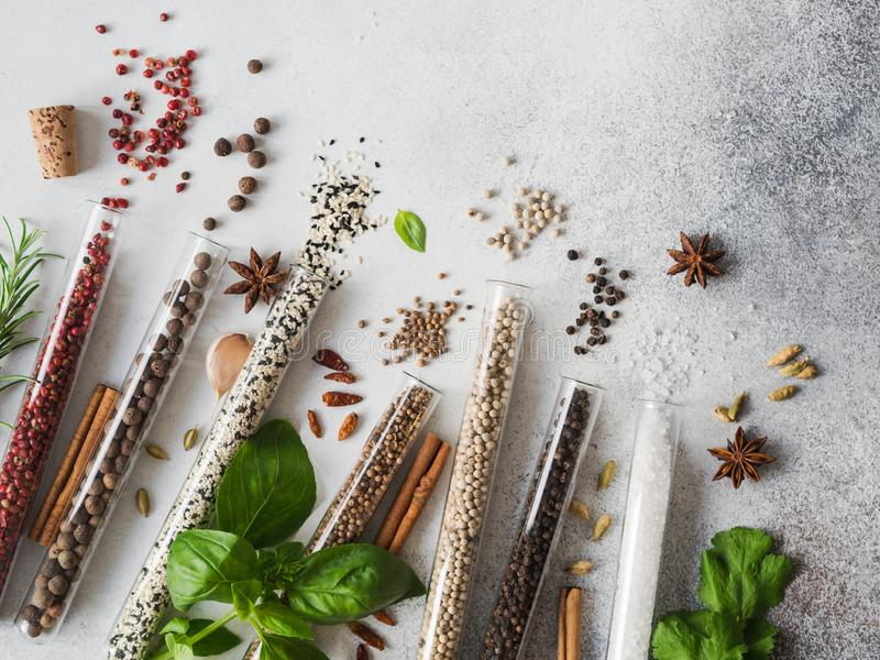 Various spices in glass test tubes and fresh herbs on gray background. Set of various spices and herbs flat lay. Top view stock photo