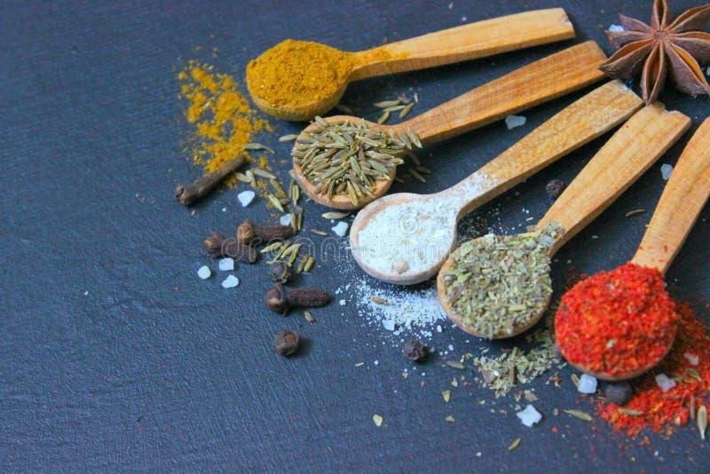 Various spices ground turmeric pepper ginger cinnamon herb seasoning salt paprika cuminin wooden vintage spoons on the black tab stock photography
