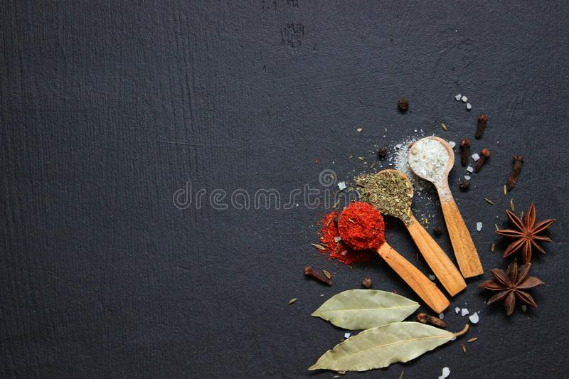 Various spices ground turmeric pepper ginger cinnamon herb seasoning salt paprika cuminin wooden vintage spoons on the black tab royalty free stock photography