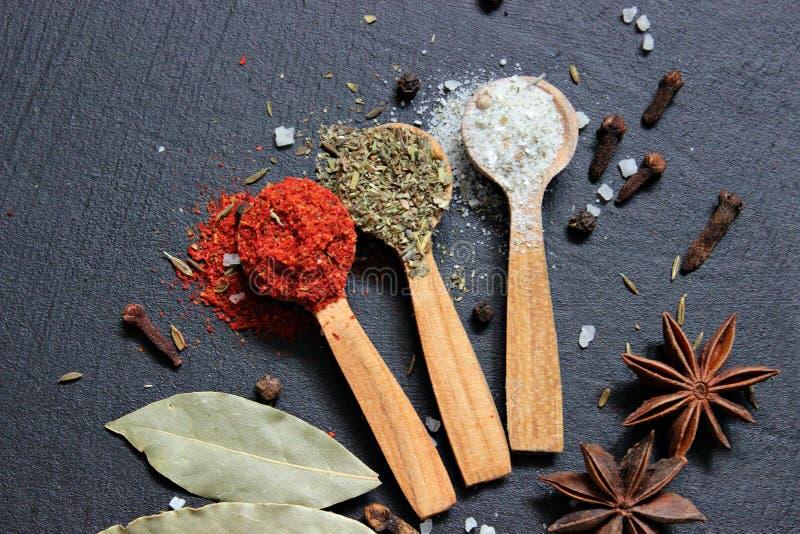 Various spices ground turmeric pepper ginger cinnamon herb seasoning salt paprika cuminin wooden vintage spoons on the black tab royalty free stock photos