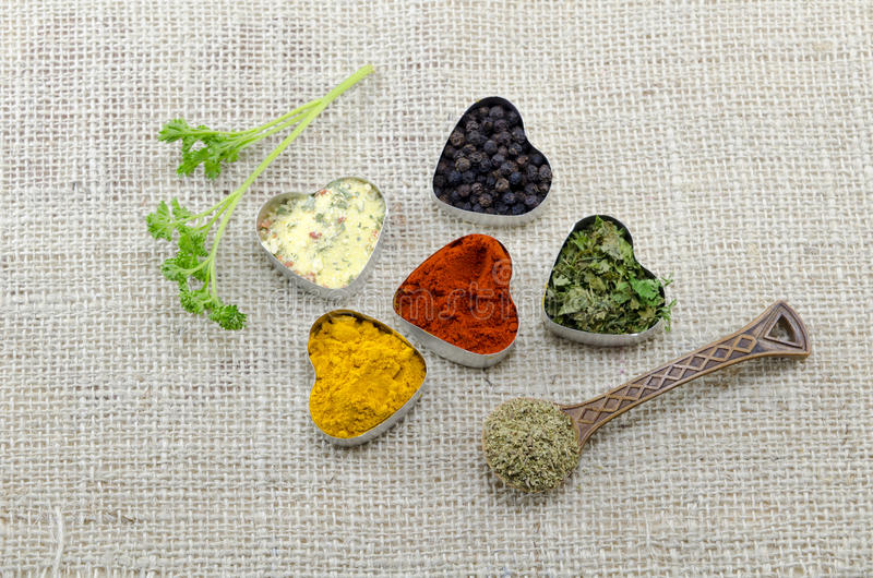 Various spices in heart chaped containers and a spoon stock image