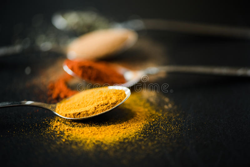 Various spices and herbs scattered in metal spoon royalty free stock photography