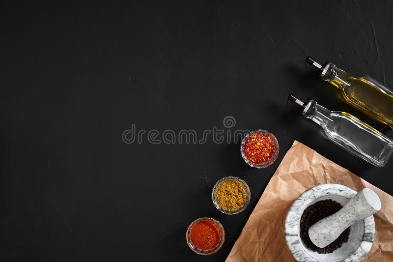 Various spices and mortar on black background with copy space royalty free stock photography