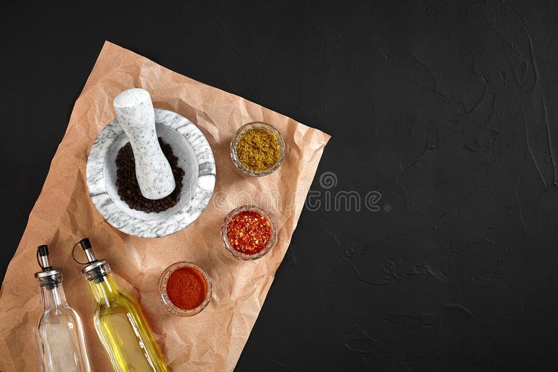 Various spices and mortar on black background with copy space royalty free stock photo