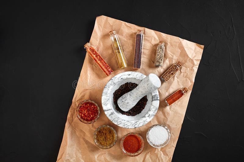 Various spices and mortar on black background with copy space stock images