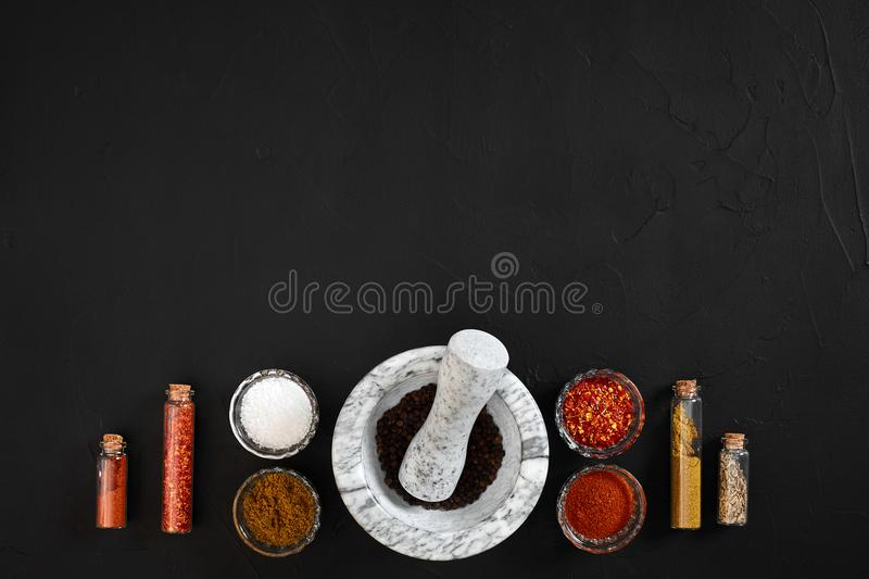 Various spices and mortar on black background with copy space stock photos
