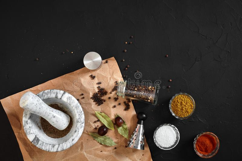 Various spices and mortar on black background with copy space stock image