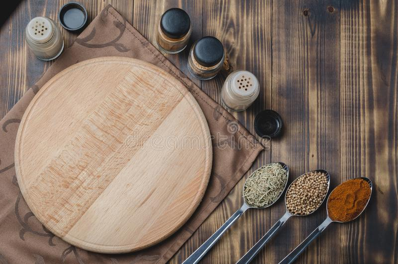 Various spices in spoons, cutting board and cooking utensils on wooden background. Top view stock photos