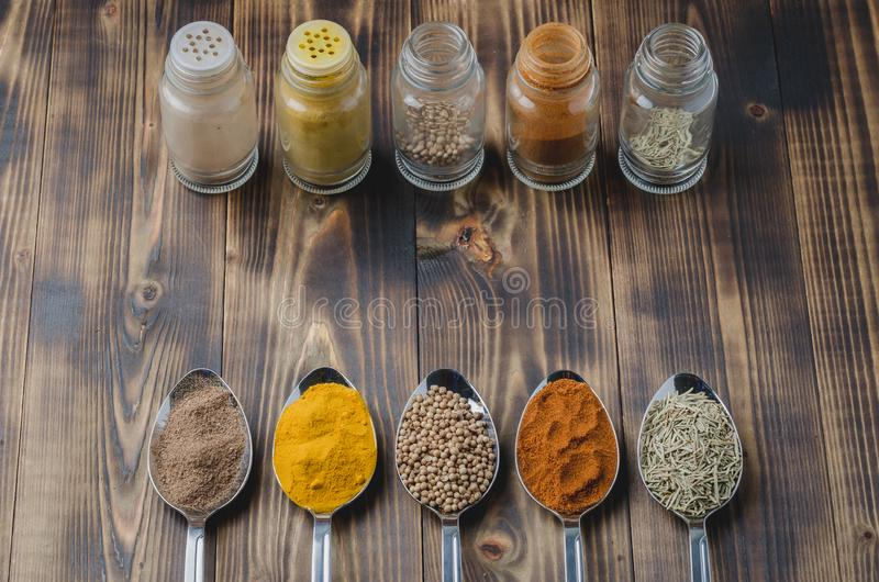 Various spices in spoons and in glass jars on a wooden table. Ingredients for cooking. Food, seasoning, cuisine, top, powder, background, dry, indian, black stock images