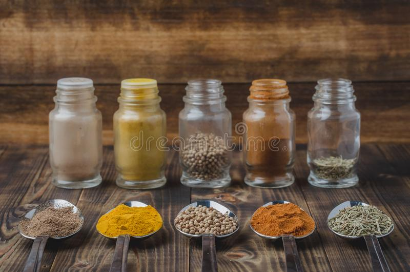 Various spices in spoons and in glass jars on a wooden table. Ingredients for cooking. Food, seasoning, cuisine, top, powder, background, dry, indian, black stock photography