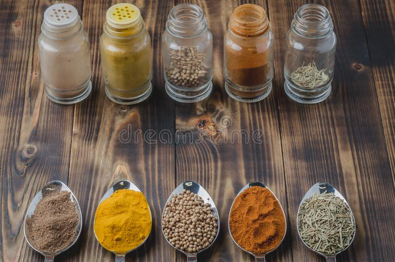 Various spices in spoons and in glass jars on a wooden table. Ingredients for cooking. Food, seasoning, cuisine, top, powder, background, dry, indian, black royalty free stock images