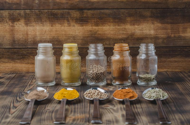 Various spices in spoons and in glass jars on a wooden table. Selective focus. Ingredients for cooking. Food, seasoning, cuisine, top, powder, background, dry stock photography