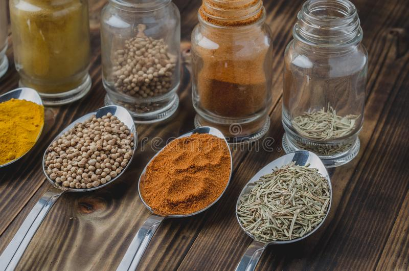 Various spices in spoons and in glass jars on a wooden table. Selective focus. Ingredients for cooking. Food, seasoning, cuisine, top, powder, background, dry stock images