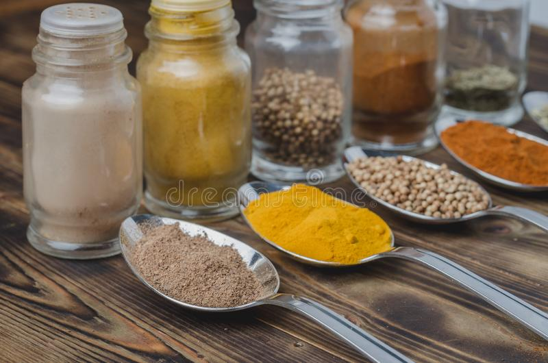 Various spices in spoons and in glass jars on a wooden table. Selective focus. Ingredients for cooking. Food, seasoning, cuisine, top, powder, background, dry royalty free stock image