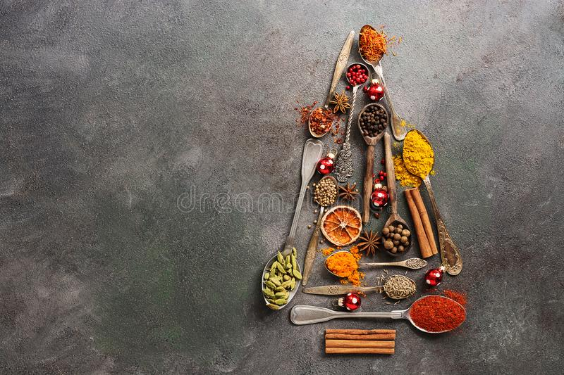 Various spices in spoons in the shape of a Christmas tree on a dark rustic background. Top view, flat lay, copy space stock photo