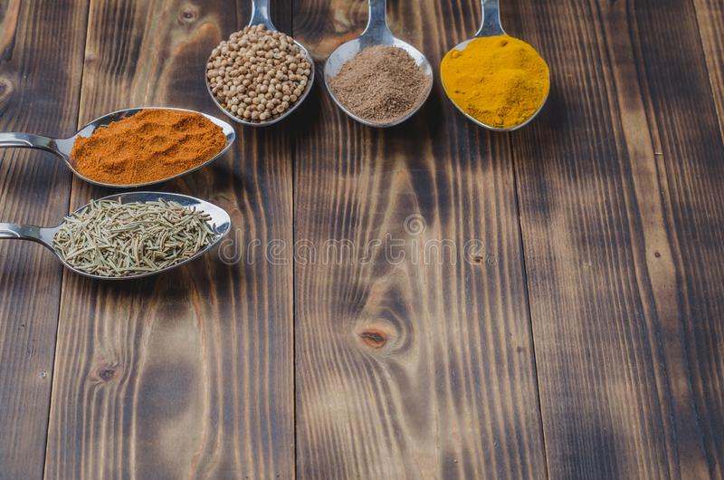 Various spices in spoons on a wooden table. Copyspace. Ingredients for cooking. Food, seasoning, cuisine, top, powder, background, dry, indian, black, kitchen royalty free stock image