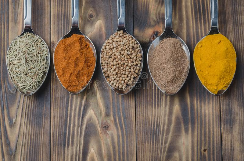 Various spices in spoons on a wooden table, top view Ingredients for cooking. Food, seasoning, cuisine, powder, background, dry, indian, black, kitchen, pepper royalty free stock photo