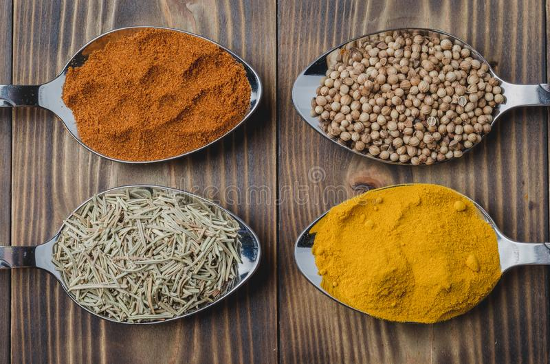 Various spices in spoons on a wooden table, top view Ingredients for cooking. Food, seasoning, cuisine, powder, background, dry, indian, black, kitchen, pepper royalty free stock photography