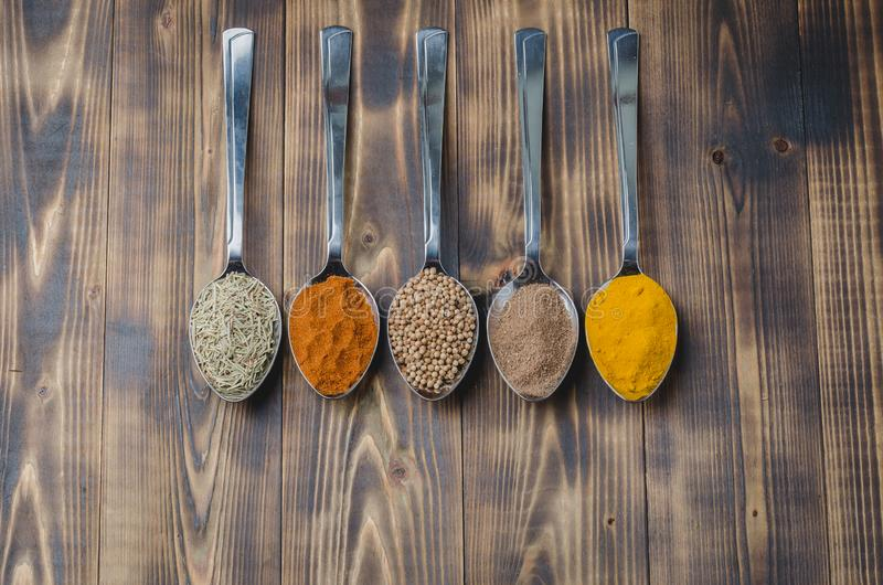 Various spices in spoons on a wooden table, top view Ingredients for cooking. Food, seasoning, cuisine, powder, background, dry, indian, black, kitchen, pepper stock image