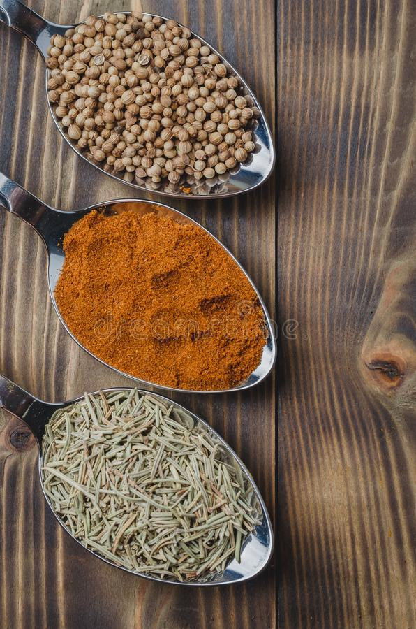 Various spices in spoons on a wooden table, top view Ingredients for cooking. Food, seasoning, cuisine, powder, background, dry, indian, black, kitchen, pepper stock photo