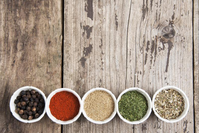 Various spices on wooden rustic background: rosemary, paprika, black pepper. Top view. Copy space. Olive oil and various spices onwooden rustic background royalty free stock photo