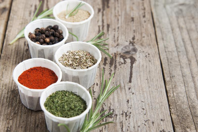 Various spices on wooden rustic background: rosemary, paprika, black pepper. Top view. Copy space. Olive oil and various spices onwooden rustic background stock photography