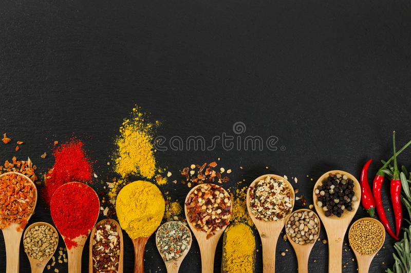 Various spices in wooden spoons on black slate background. royalty free stock photos