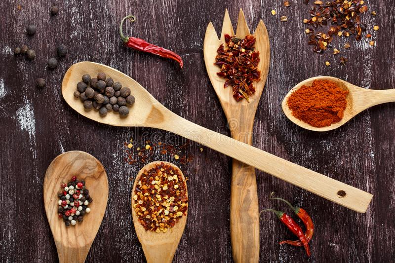 Various spices in wooden spoons on dark brown background. Different types of paprika and peppercorn. Top view stock photography