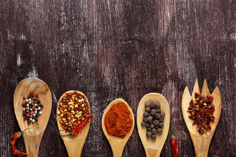 Various spices in wooden spoons on dark brown background. Different types of paprika and peppercorn. Top view. Copy space stock image