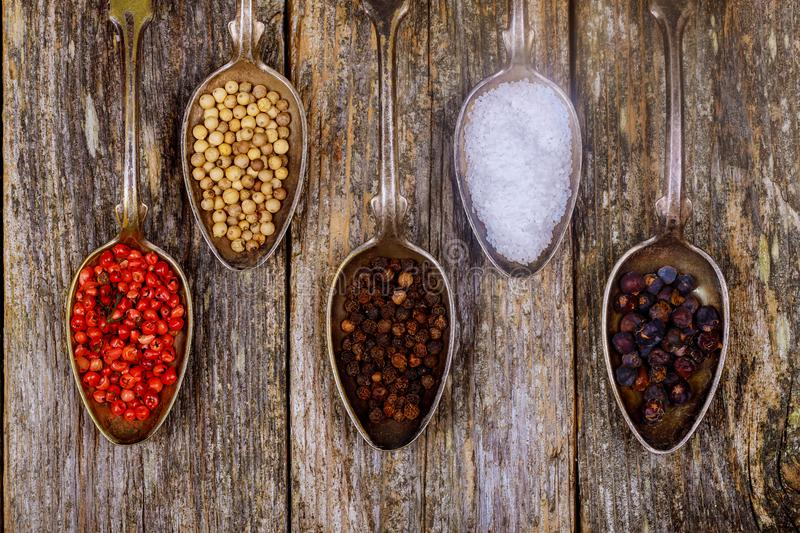 Various spices in wooden spoons on dark brown background. Different types of paprika and peppercorn stock images