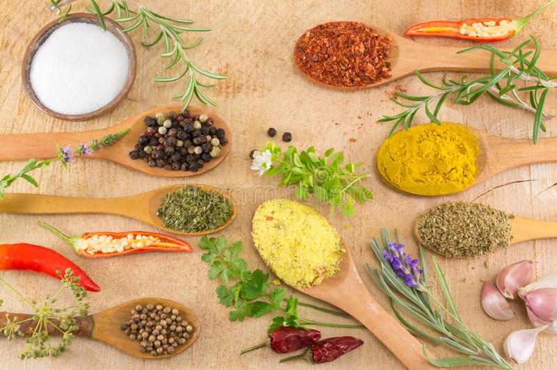 Various spices in wooden spoons on wooden table royalty free stock photos