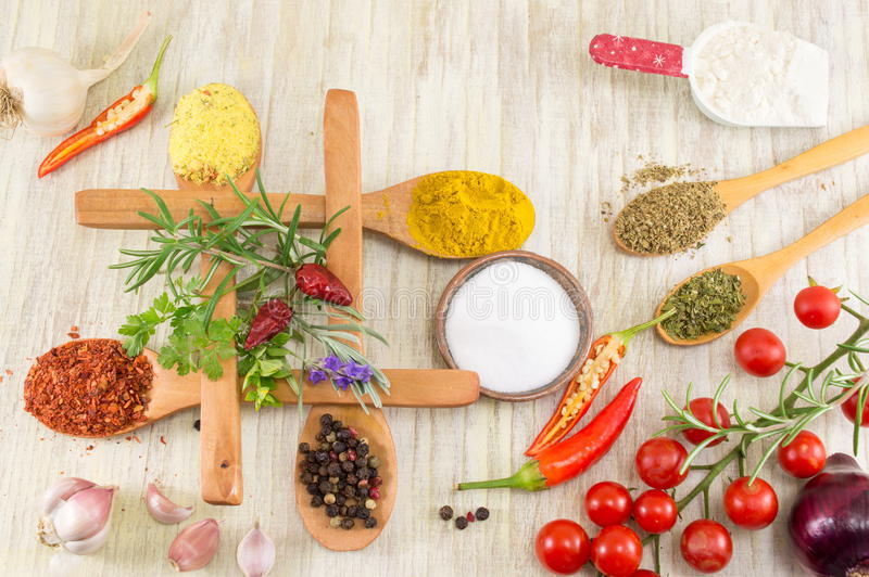 Various spices in wooden spoons on wooden table royalty free stock images