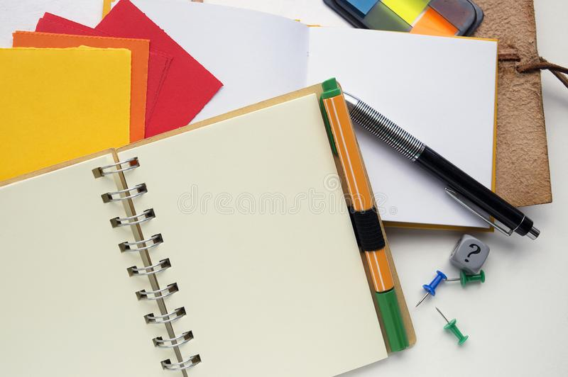 Various stationary objects: spiral bound notebook, pens, notebooks, dice with a question mark, pins, sticky notes. royalty free stock photo