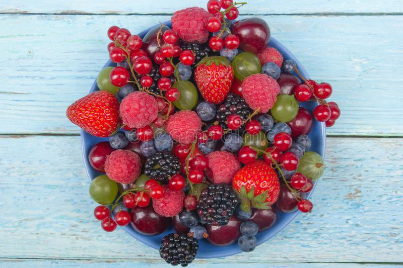 Various summer Fresh berries in a bowl on rustic wooden table. Antioxidants, detox diet, organic fruits. stock photography