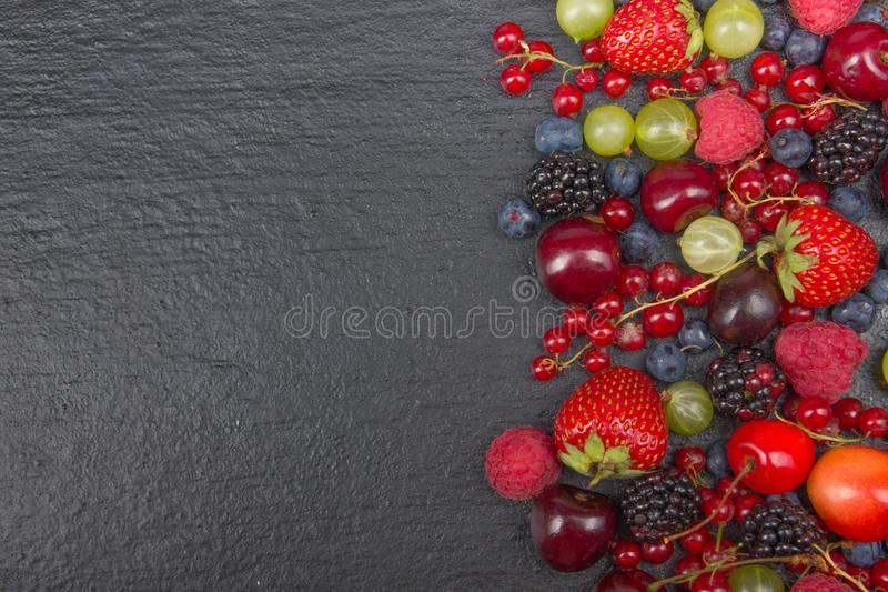 Various summer Fresh berries in a bowl on rustic wooden table. Antioxidants, detox diet, organic fruits. Top view royalty free stock photos